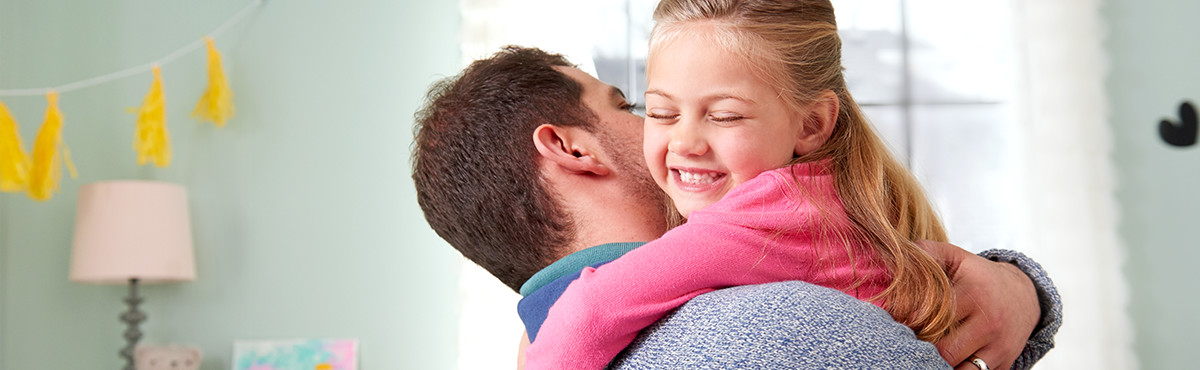 Dad holding daughter after having heart to heart about wetting the bed, Therefore lessening the burden