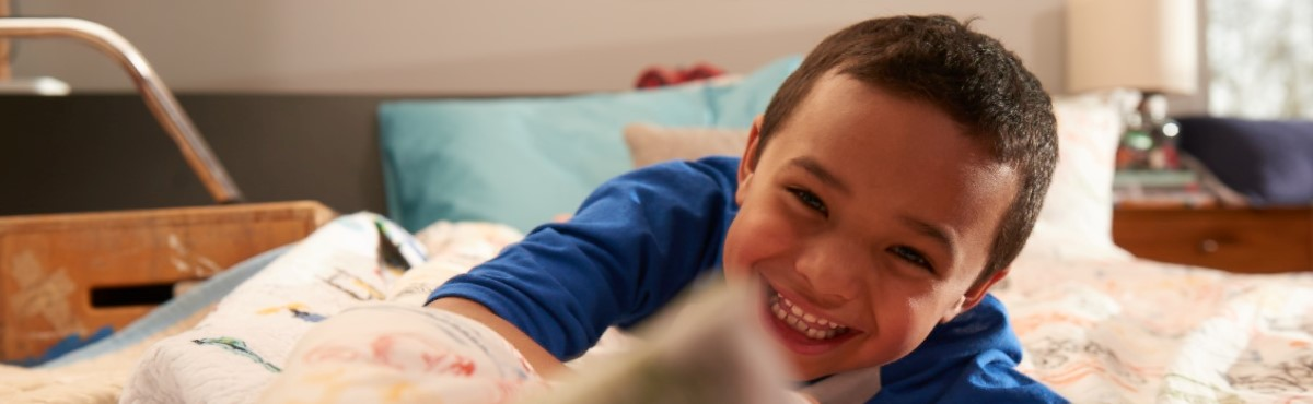 A young boy laying in bed smiling.