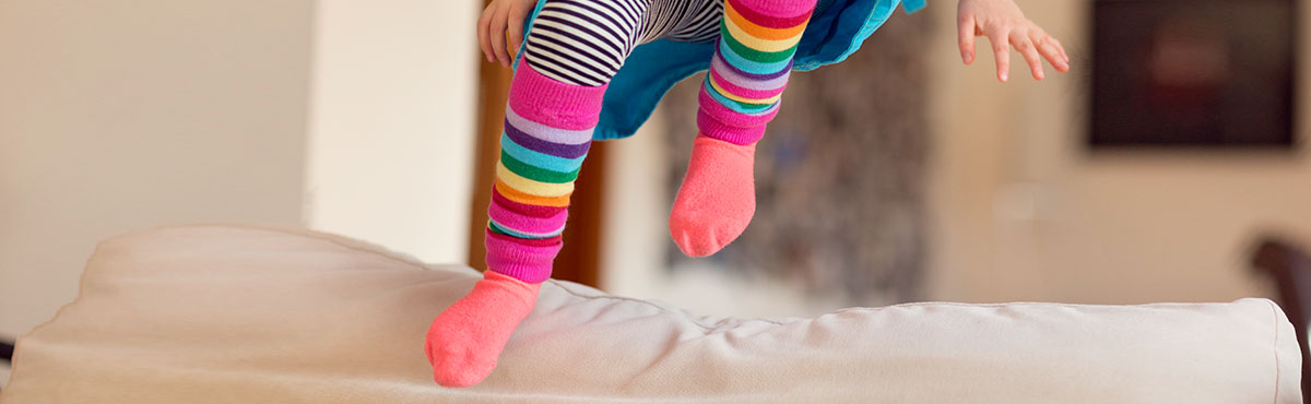 Picture of a child jumping on their bed wearing very colorful socks