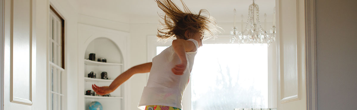 A child captured mid-air jumping on a bed