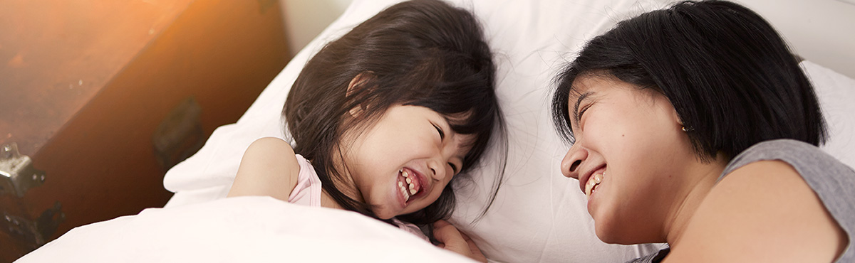 Mother and daughter laughing in bed