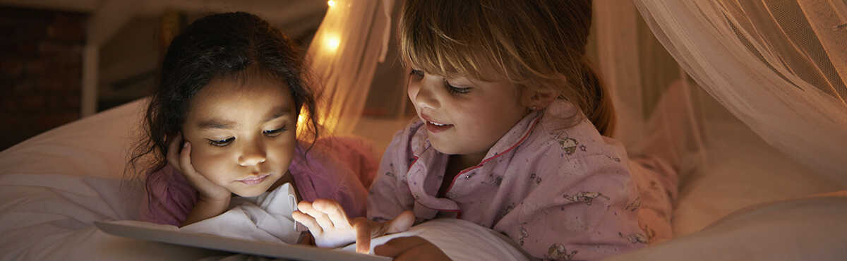 Girls playing with iPad on a bed during a sleepover