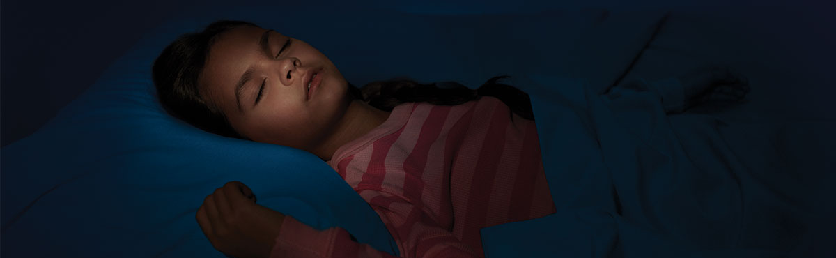 Girl sleeping soundly in her bed wearing a pink stripped pajama shirt